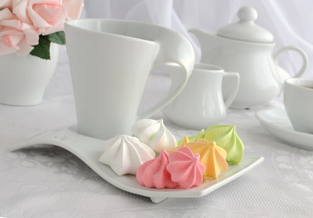 Meringue cookies of different colors on a plate with a cup of co