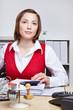 Frau sitzt ernst am Schreibtisch