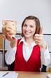 Frau hält Daumen hoch mit Sparschwein