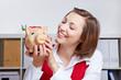 Lachende Frau schaut Sparschwein an