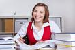 Lachende Frau lernt am Schreibtisch