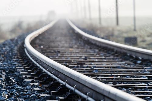 Leinwandbild Motiv Einspurige Bahnlinie im Morgennebel
