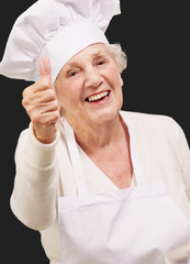 portrait of cook senior woman doing approval gesture over black