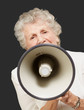 portrait of senior woman screaming with megaphone over black bac