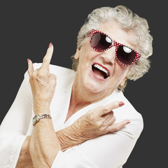 portrait of senior woman doing rock symbol over black background