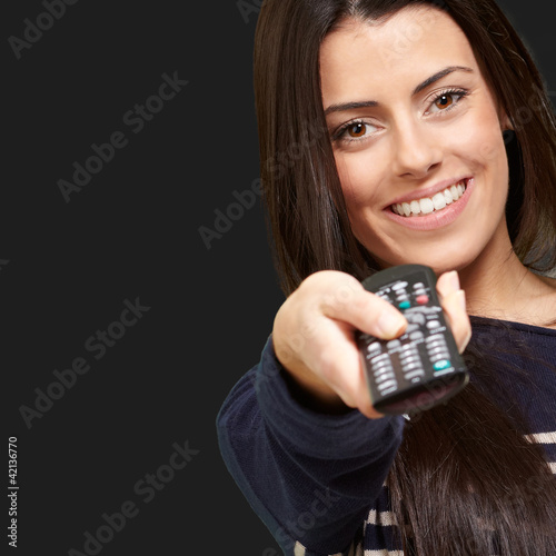 young girl changing channel over black background