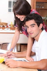 Couple writing on the kitchen table