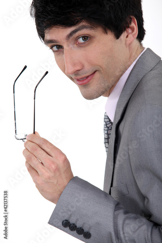 Businessman holding his glasses