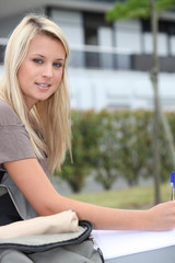 Female student sat outdoors studying
