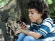 Beautiful curly child playing with cellphone sitting in the park