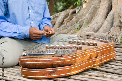Playing a khim musical instrument, Cambodia