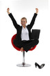 Excited blond businesswoman sat barefoot in chair