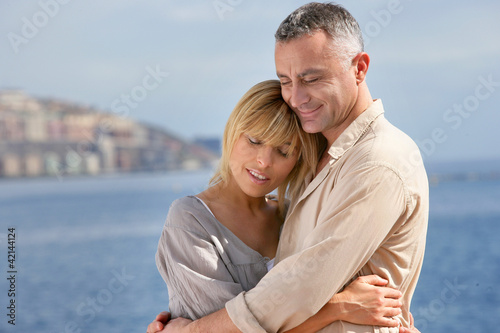 Couple hugging by the sea