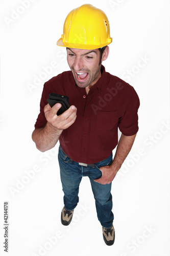 Angry builder shouting down mobile telephone