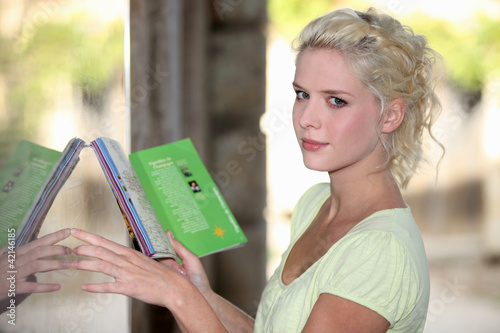 Blond woman reading restaurant menu