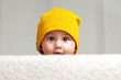 Cute Baby with a Beanie Hat behind a Sofa