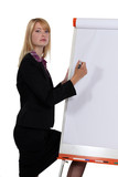 businesswoman writing with a marker on a board