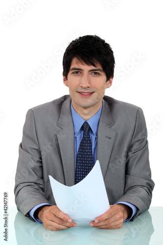 businessman sitting at his desk holding a sheet of paper