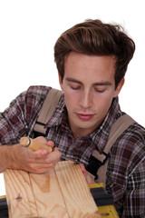 Carpenter using a chisel to sculpt wood