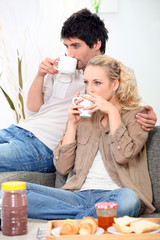 Couple having breakfast on the couch