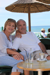 Couple sitting at a beachside cafe
