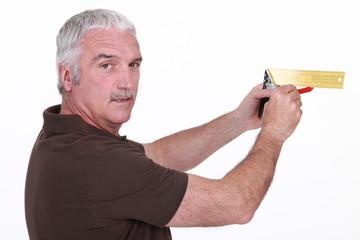 Elderly man marking wall as