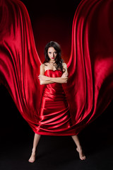 Mysterious  woman in red waving silk dress over black background