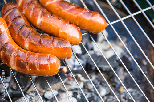 Tasty sausages burning on hot barbeque