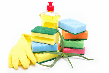 Detergent bottle, rubber gloves and cleaning sponge on a white b