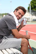 Tennis player sat on bench