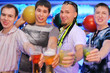 Four men hold balls and glasses of beer and cocktail in bowling