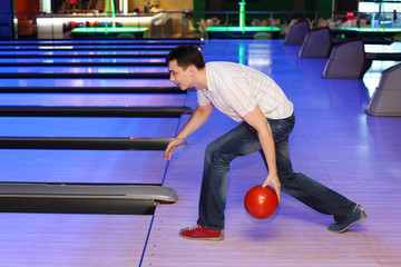 Young man wearing jeans throws ball in bowling; profile of man