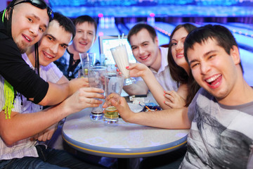 Company of happy friends sit at table and drink beer in bowling;
