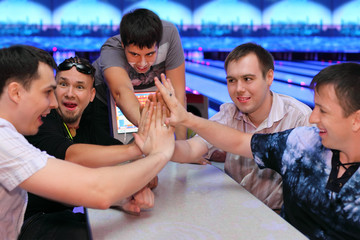 Five happy men sit at table and touch hands in bowling; focus on