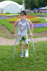 Sad boy on crutches in beautiful summer park; leg in cast