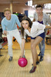 Young smiling woman throws ball in bowling;