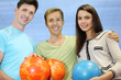 Two men and woman hold orange and blue balls in bowling club