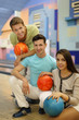 Two happy men and girl hold balls in bowling club; focus on girl