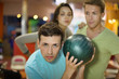 Young man prepares to throw of ball in bowling
