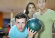 Young man prepares to throw of green ball in bowling;