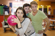 Woman prepares to throw of pink ball in bowling;