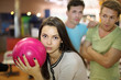 Woman prepares to throw of ball in bowling; two men look at her;