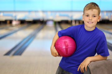 Happy boy dressed in T-shirt holds pink ball in bowling club