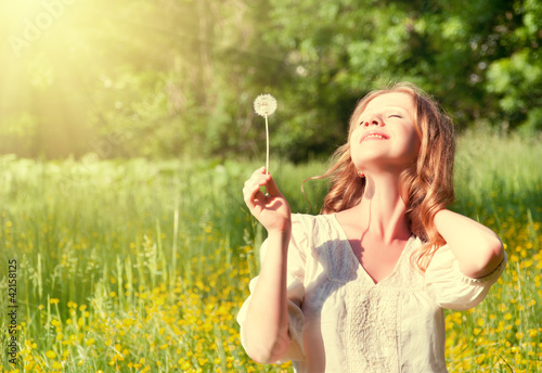 beautiful girl with dandelion enjoying the summer sun