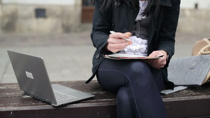 Student working on laptop and writing notes in the city