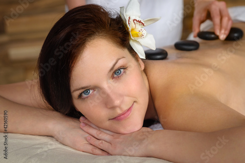 Woman enjoy hot lava stone massage spa