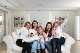 Women cheering on the sofa