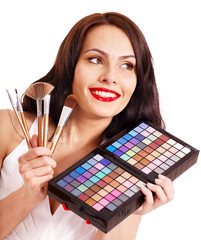 Girl holding eyeshadow and makeup brush.