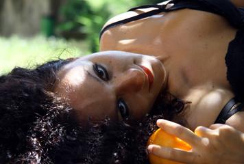 modella sdraiata al parco con arance