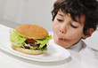 Kid on temptation with delicious hamburger